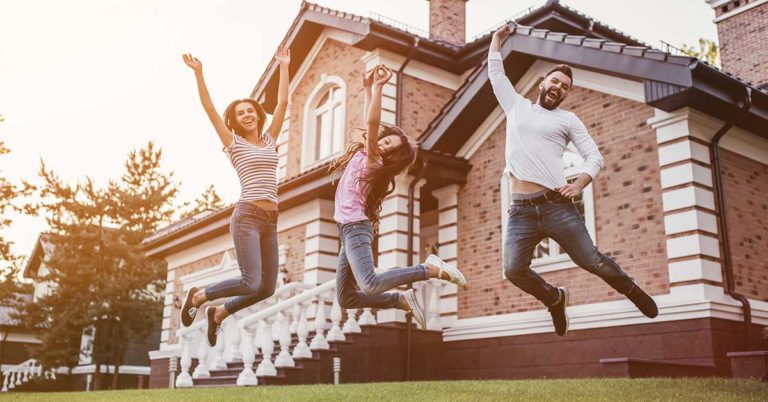 image of a family jumping together in front of a house