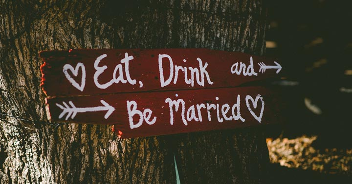how to pay for a wedding without going broke; sign attached to a tree that reads eat, drink, and be married