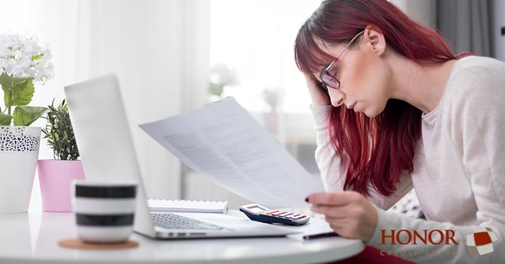 a few simple tips can help you maintain a balanced budget as a new college graduate; woman staring at papers at a desk