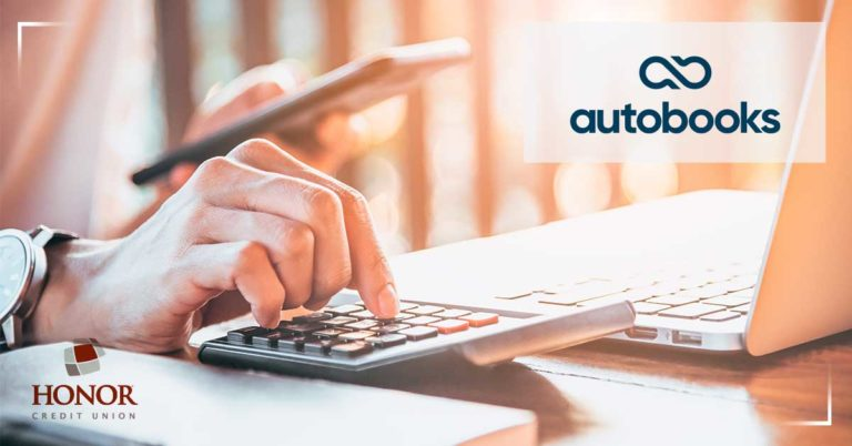 simplify your business accounting with the help of honor credit union and autobooks; hand holding phone while other hand types on calculator