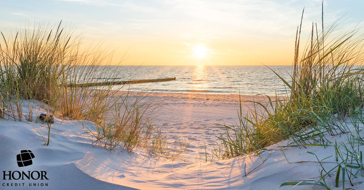 A picture of a sandy beach at sunset with Honor Credit Union's logo in the bottom left corner.