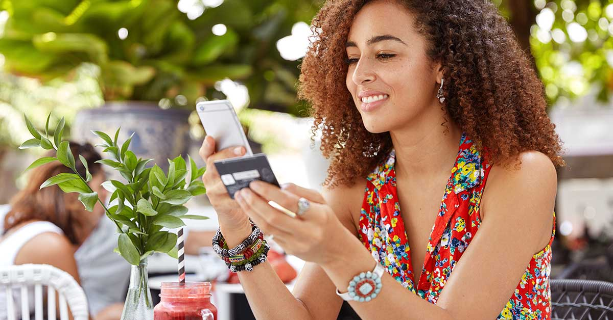 photo of a woman in her 20s looking at her credit card while holding a mobile phone in her other hand