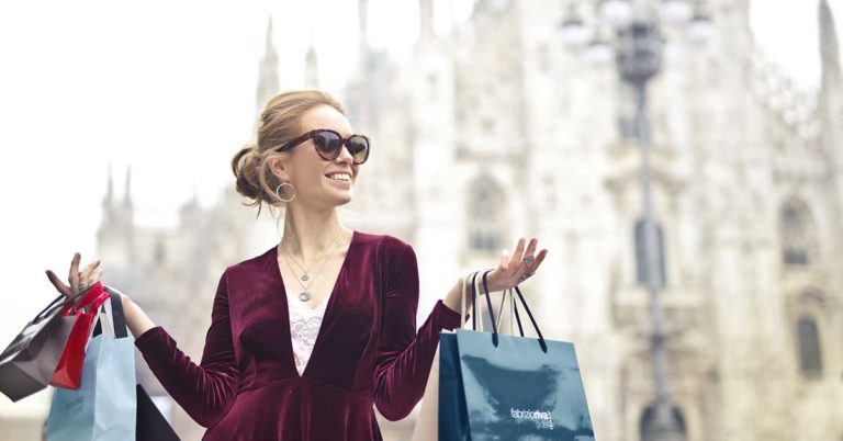 know when and where to buy foreign currency, and why it's important to know exchange rates; photo of woman shopping in a foreign country