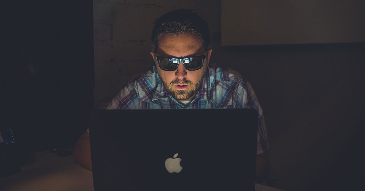 there are practical ways to protect your online identity and profiles; photo of man wearing sunglasses in dark room typing on computer