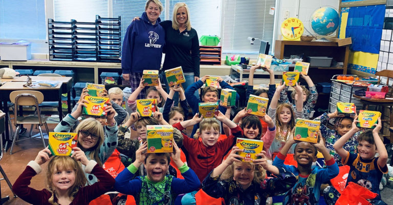 honor credit union announced 40 teacher award winners for 2019; group of students holding boxes of crayons in a classroom