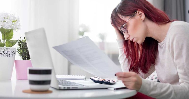 transfer a credit card balance to honor credit union; woman looking at papers at a table with a calculator