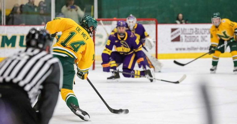 a northern michigan hockey player shoots the puck against minnesota state; honor credit union partners with NMU to donate money for each goal scored at home hockey games