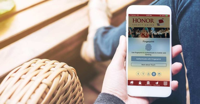 log in to the honor credit union app using a pin, fingerprint, facial recognition, voice, or a traditional password; image of a hand holding the honor app using the fingerprint login method