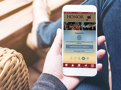 logging in to the honor app is simple with biometric authentication; photo of a hand holding a mobile phone with the honor credit union mobile app open