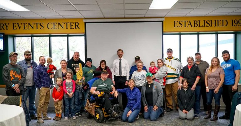 image of northern michigan university hockey coach and players posing for photo with military veterans and other non-profit organization representatives at a check presentation