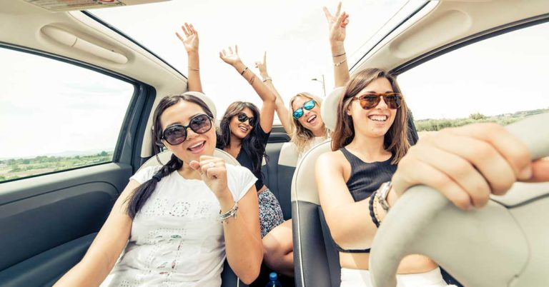 photo of a group of girls having fun riding in a car on a sunny day