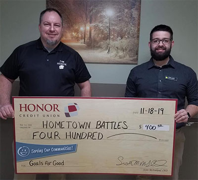 honor credit union's jamie gollakner presents a check to hometown battles non-profit organization