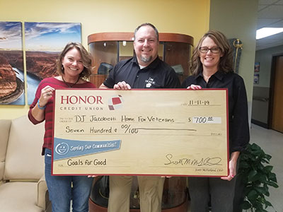 image of jamie gollakner from honor credit union presenting a check to the jacobetti veterans home