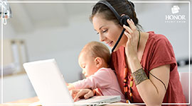 woman talking on the phone while holding a baby and looking at a laptop