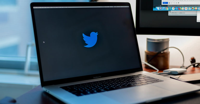 photo of a laptop resting on a desk displaying the Twitter logo