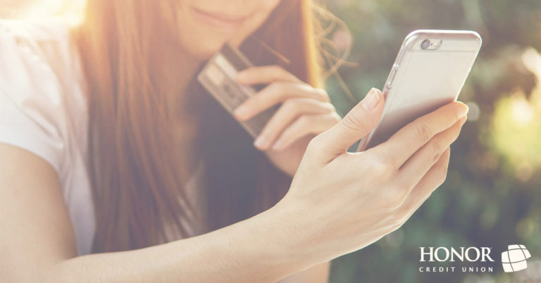 image of a woman holding a mobile phone in one hand and a credit card in another hand