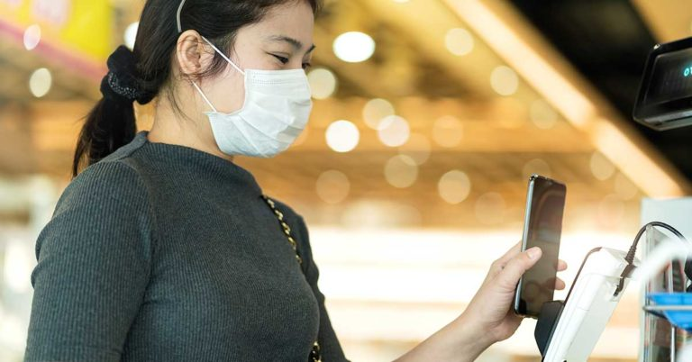 image of a woman wearing a medical face mask holds her phone up to a credit card terminal to make a touchless payment