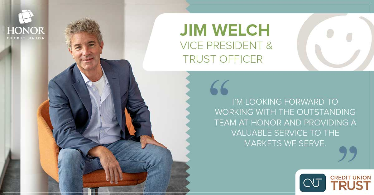 photo of CU Trust Vice President Jim Welch wearing jeans and a blue suit coat sitting in a orange chair