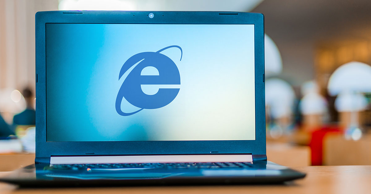 image of a laptop resting on a table with the internet explorer logo displaying on the laptop screen