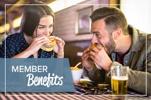 image of a man and woman eating food at a bar with text on the image promoting benefits for honor credit union members