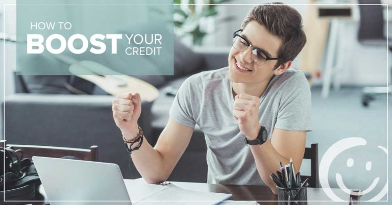 image of a man sitting at a desk looking at a laptop while smiling and clenching his fists