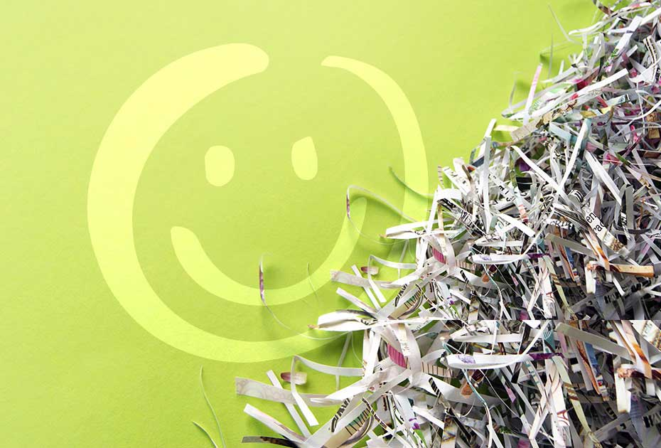 image featuring a stack of shredded paper sitting next to a green wall that has a white smiley face on it