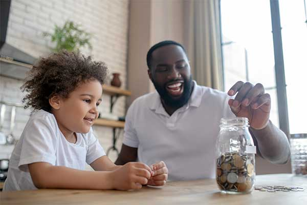 photo of a father and daughter putting loose change in a glass jar at a table