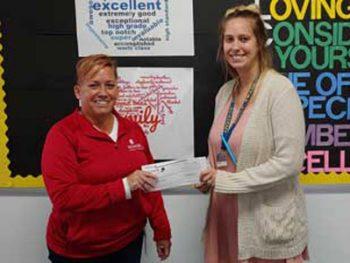 Honor's Julie Lord presenting a Marshall Academy teacher with her $100 Teacher Award