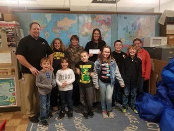 Honor's Jamie Gollakner presenting Gwinn Community School's Hope Bruce and students with $100 Teacher Award
