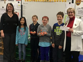 Honor's Tanya Urias presenting St. Joseph Public School's Mrs. Jarvie and students with $100 Teacher Award