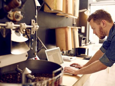 Small business owner of roastery checking his laptop