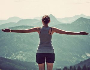 woman standing with her arms out looking at a mountain landscape